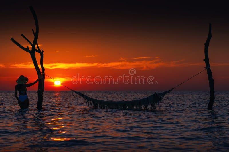 Belle silhouette de jeune femme avec l'oscillation posant en mer sur le coucher du soleil, paysage romantique maldivien photographie stock libre de droits