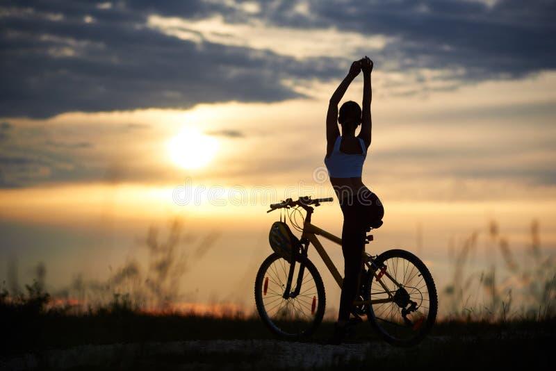Belle silhouette de vue arrière de femelle parfaite de corps contre le ciel de soirée de fond avec le coucher de soleil images stock