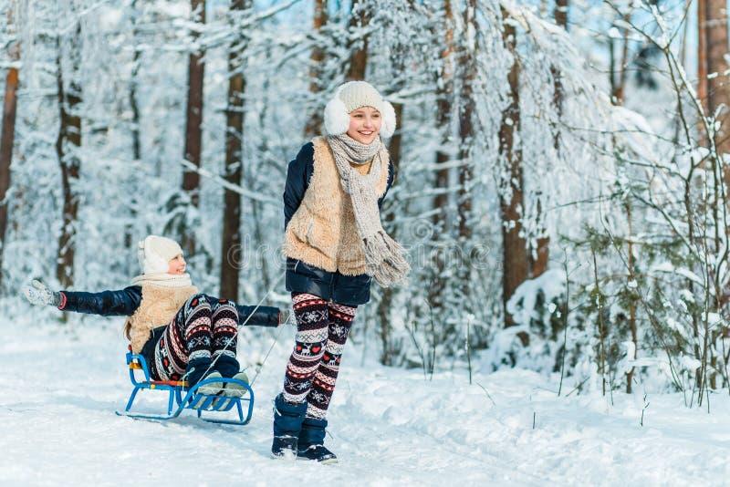 Belle sorelle dei gemelli degli adolescenti che guidano slitta e che si divertono fuori in un legno con neve Concetto di amicizia fotografia stock