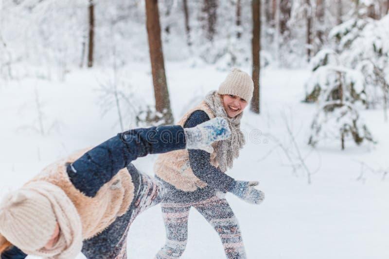 Belle sorelle dei gemelli degli adolescenti divertendosi fuori in un legno con neve nell'inverno Amicizia, famiglia, concetto fotografia stock libera da diritti