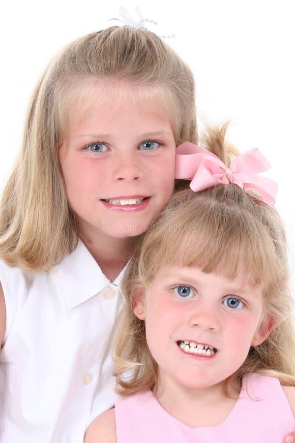 Belle sorelle nel colore rosa sopra bianco fotografia stock libera da diritti