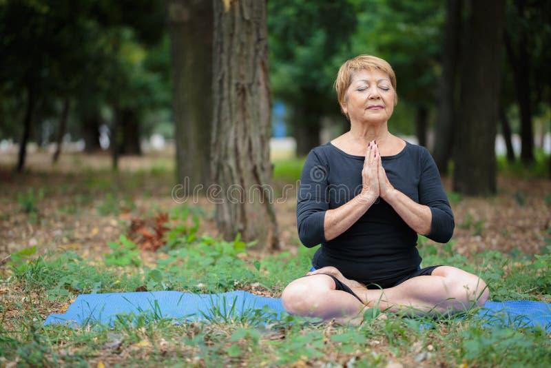 Belle, souriante femme supérieure en position de lotus sur un fond de parc le concept remet son ciel augmenté par méditation d'ho images stock