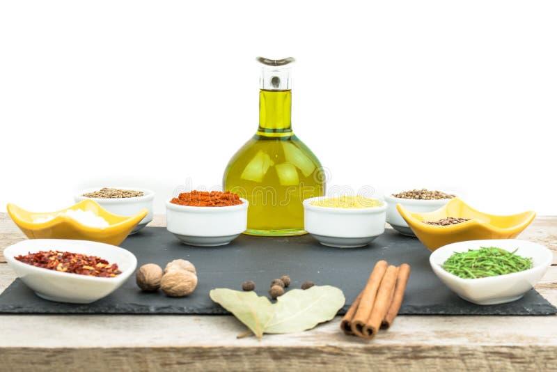 Belle spezie variopinte in ciotole sul vassoio, sull'olio d'oliva e sul sale dell'ardesia Spazio libero per il vostro testo fotografia stock