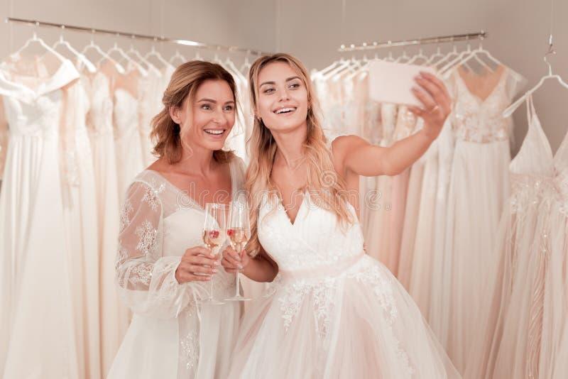 Belle spose positive che posano per una foto fotografia stock