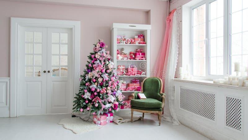 Belle stanze decorate holdiay con gli alberi di Natale, lo scaffale ed i regali blu rosa su, interno verde della casa della sedia fotografie stock libere da diritti
