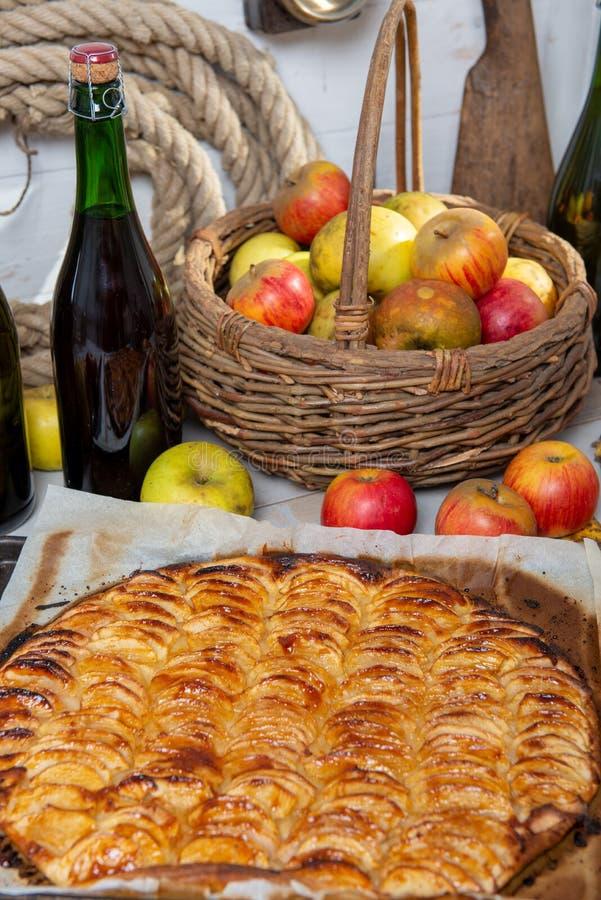 Belle tarte aux pommes avec des pommes et bouteille de cidre images stock