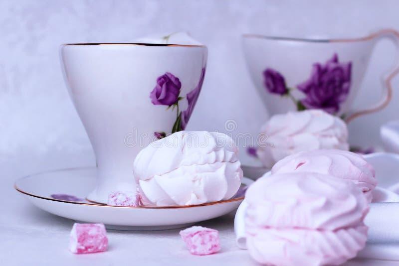 Belle tasse avec des supports d'ornement de fleur sur la table Sont tout près les morceaux dispersés de bonbons et de guimauves o image stock