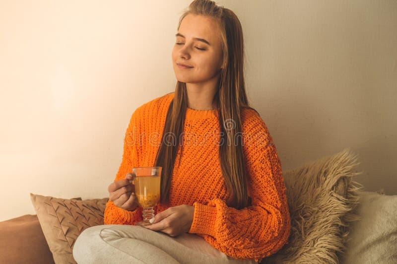 Belle tasse heureuse de boissons de jeune femme de café ou de thé Dans le lit dans un chandail orange lumineux Verticale de plan  images stock