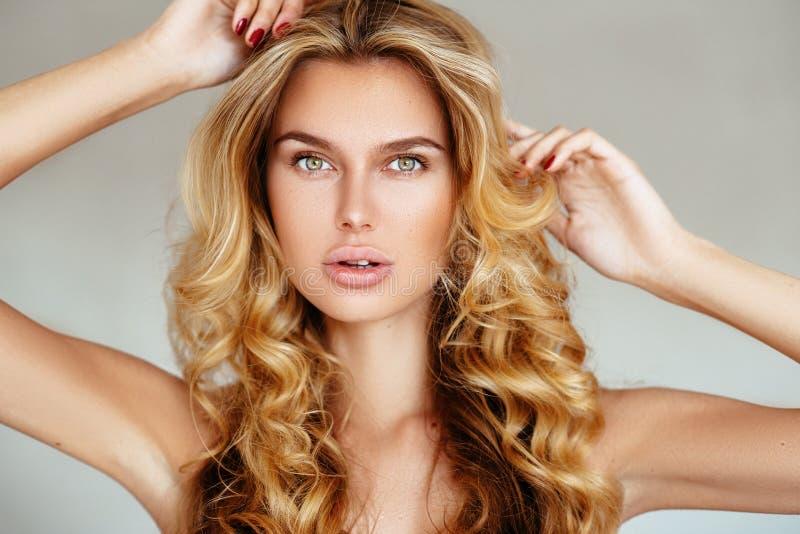 Belle, tendre, sexy fille blonde avec de longs cheveux et lèvres gonflées sans maquillage posant dans la lingerie rose sur un fon images stock