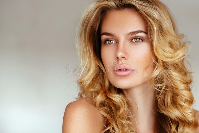 Belle, tendre, sexy fille blonde avec de longs cheveux et lèvres gonflées sans maquillage posant dans la lingerie rose sur un fon photographie stock libre de droits