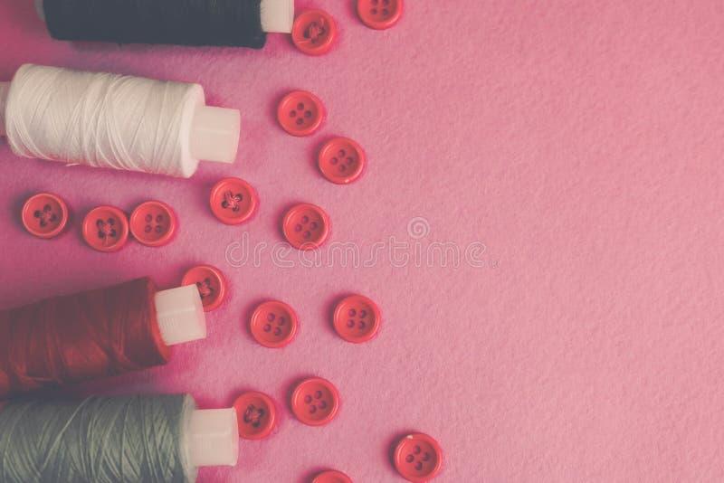 Belle texture avec un bon nombre de boutons rouges ronds pour la couture, la couture et les écheveaux des bobines du fil Copiez l photos libres de droits