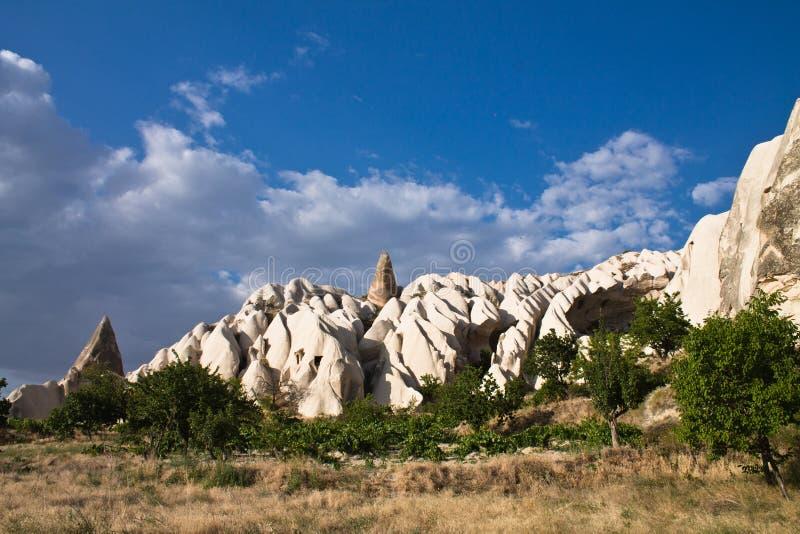 Belle troglodite della valle rocciosa della rosa del deserto in cielo blu con le nuvole fotografia stock