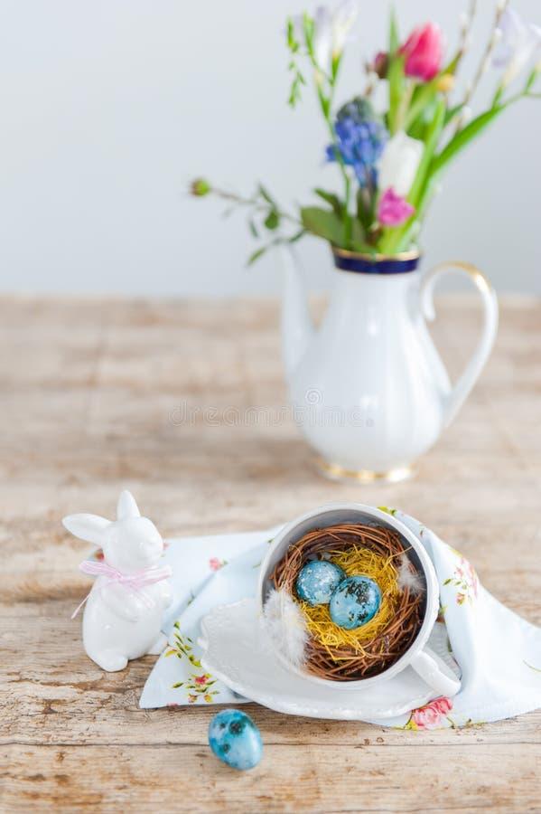 Belle uova di Pasqua macchiettate luminose in un nido da una tazza nella priorità alta Lepri della porcellana e un vaso con i fio immagine stock libera da diritti