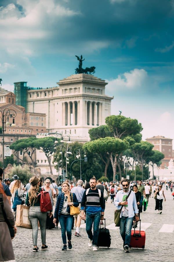 Belle vecchie finestre a Roma (Italia) Turisti che portano le valigie vicino all'altare della patria sulla piazza Venezia fotografia stock