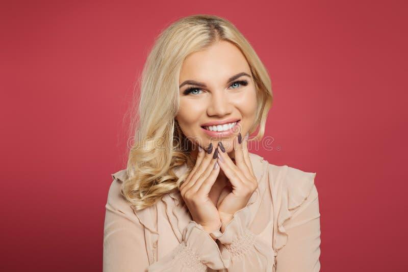 Belle verticale de jeune femme Tir de studio de fille assez blonde de cheveux bouclés sur le rose, plan rapproché de visage images libres de droits