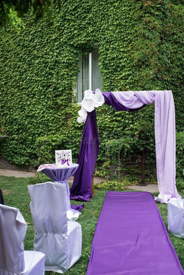 Belle voûte carrée de mariage, décorée du matériel blanc et de la verdure, se tenant dans le jardin pour des nouveaux mariés et l photo libre de droits