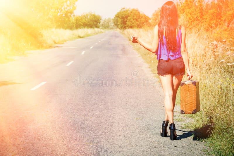 Belle voyageuse de fille de brune avec la valise sur la route, faisant de l'auto-stop Concept de voyage, aventure, vacances, libe photographie stock