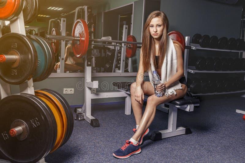 Belle vraie fille sportive naturelle se reposant sur le banc de boucle de prédicateur images libres de droits