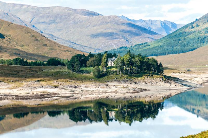 Belle vue avec la maison écossaise en montagnes lac et forêt photos libres de droits