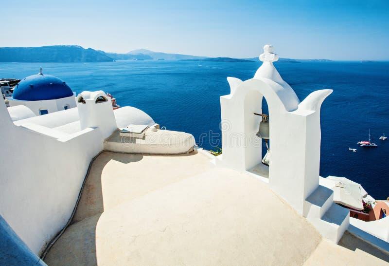 Belle vue d'horizon de Santorini Mer bleue, ciel et église blanche avec le toit bleu photographie stock libre de droits