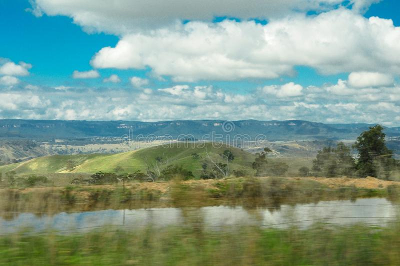 Belle vue de colline verte de campagne d'Australie avec le ciel nuageux images libres de droits