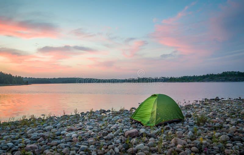 Belle vue de coucher du soleil sur le lac calme et la petite tente de touristes images stock