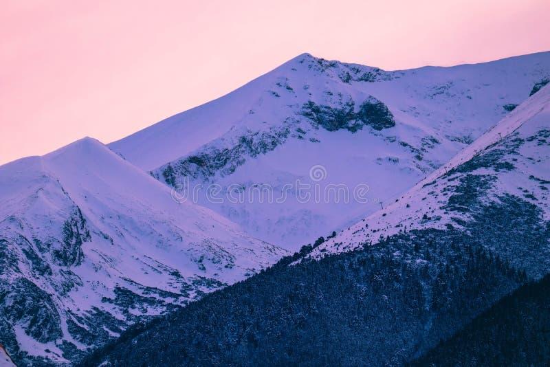 Belle vue de coucher du soleil sur les crêtes de montagnes élevées d'hiver, sur photo libre de droits