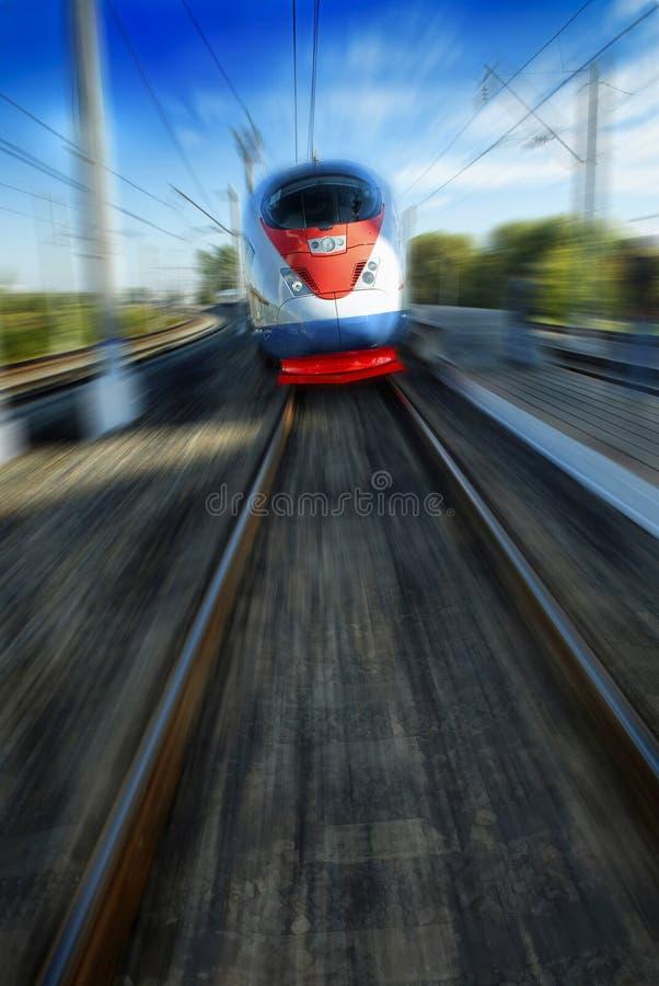 Belle vue de face impressionnante étonnante sur le beau train de voyageurs à grande vitesse bleu rouge blanc mobile dans la tache images libres de droits