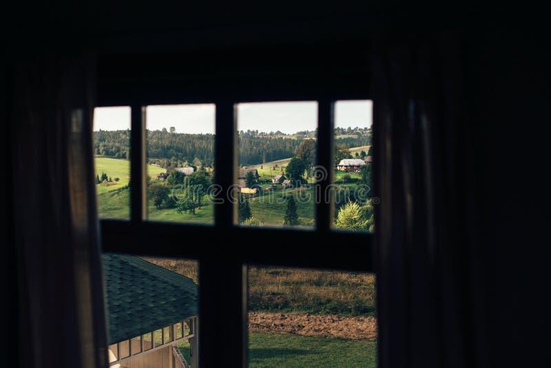 Belle vue de fenêtre de cabine sur les collines vertes de montagne avec la forêt et les maisons en bois dans le jour ensoleillé A photos stock