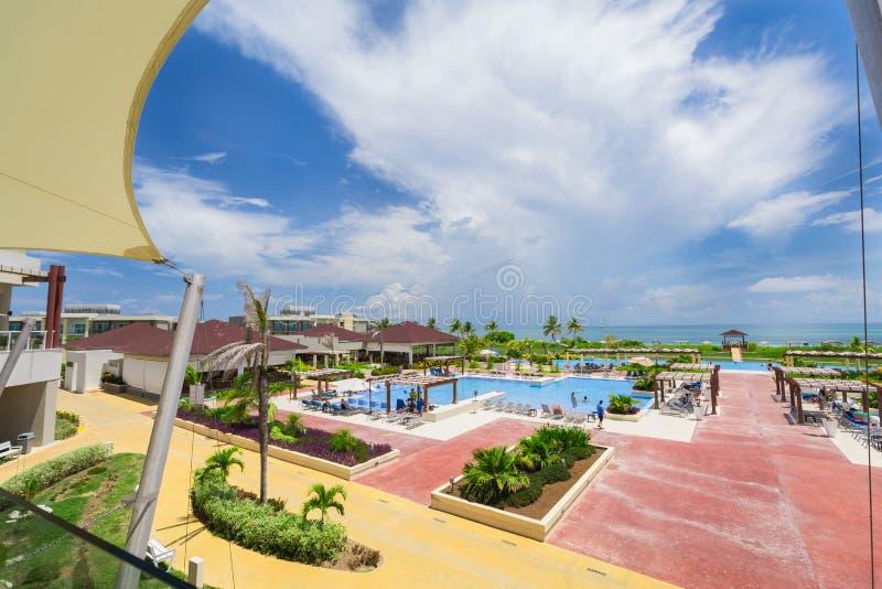 Belle vue de invitation de grande piscine confortable grande ouverte sur le fond d'océan et de ciel bleu photographie stock libre de droits