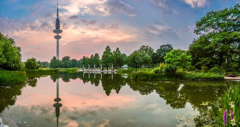 Belle vue de jardin d'agrément en parc de Planten um Blomen avec la tour célèbre de Heinrich-Hertz-Turm au crépuscule, Hambourg,  image stock