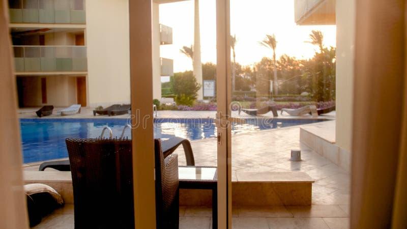 Belle vue de l'intérieur de villa luxueuse sur des lits et des canapés du soleil à la piscine et au beau ciel de coucher du solei image stock