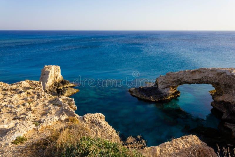 Belle vue de la mer Méditerranée bleue et de la voûte de roche un jour ensoleillé de cap Greco en Chypre Paysage en pierre d'Ayia images stock
