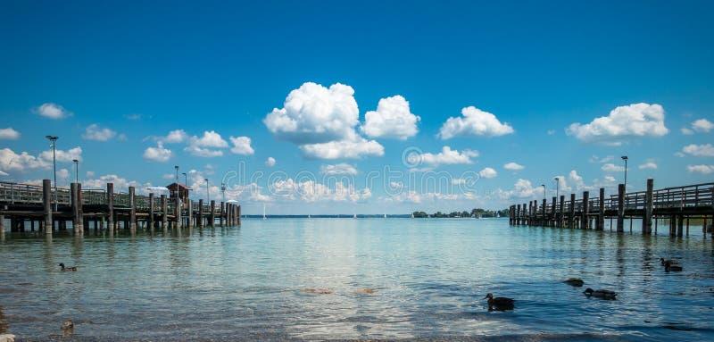 Belle vue de lac Chiemsee, avec le pilier en bois, le ciel nuageux bleu et les canards image stock