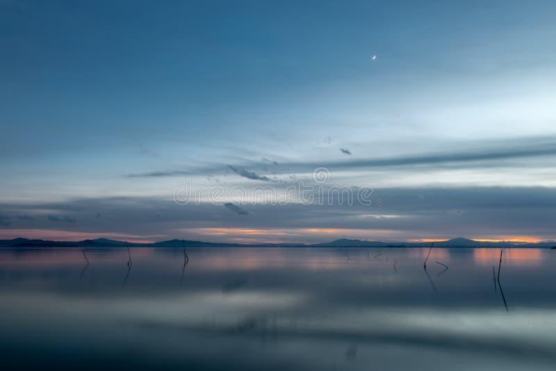 Belle vue de lac Ombrie, Italie Trasimeno au crépuscule, avec les tons bleus et oranges et la lune dans le ciel photo stock