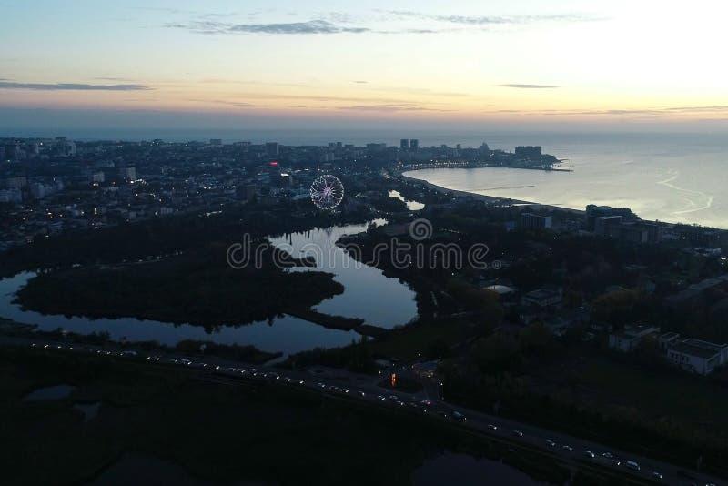 Belle vue de nuit de ville côtière avec la rivière coulant dans la mer sur le coucher du soleil photographie stock