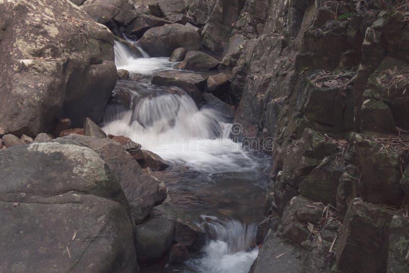 Belle vue de paysage de petite cascade en rivière avec le courant de l'eau traversant la pierre située dans la forêt tropicale photographie stock
