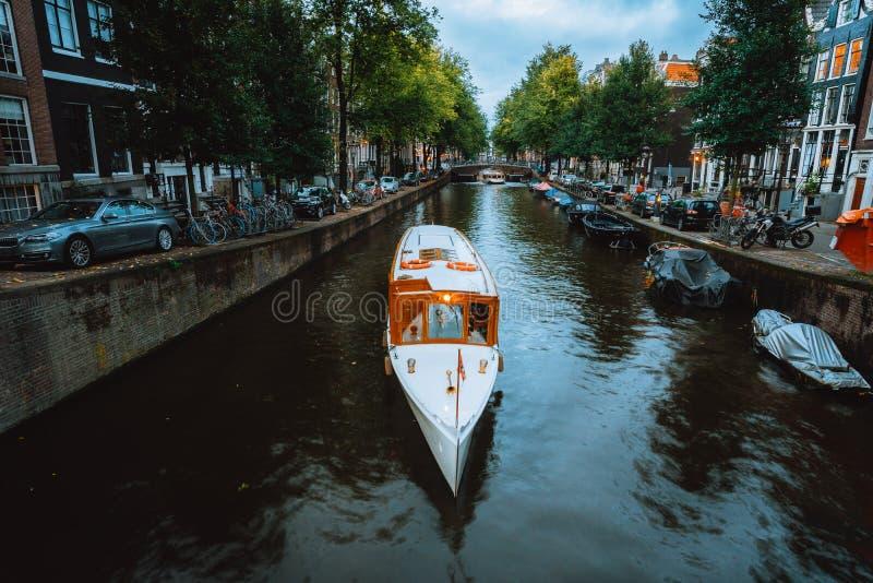 Belle vue des canaux d'Amsterdam avec le pont en bateau blanc de croisi?re et les maisons n?erlandaises typiques holland photos stock