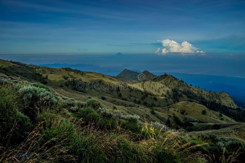 Belle vue des champs verts avec des collines et des nuages de montagnes et de stupéfier sur l'horizon photo stock