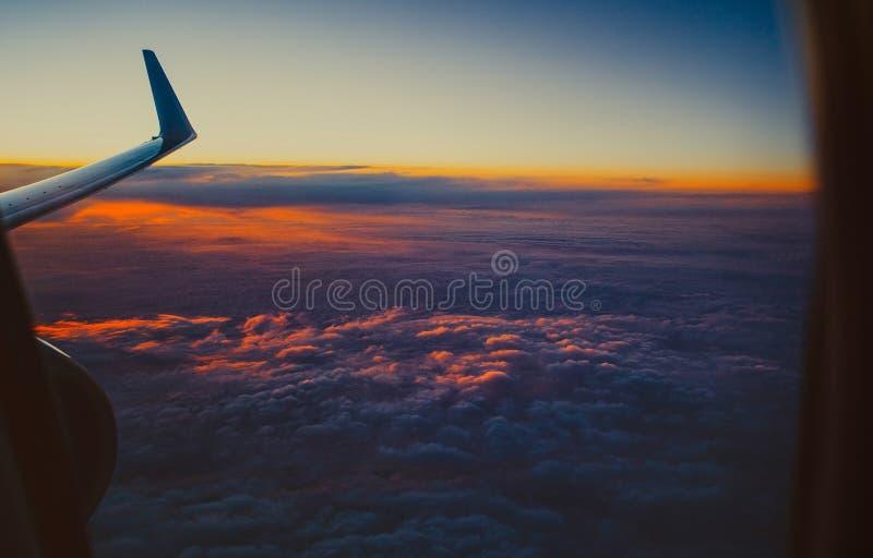 Belle vue du hublot de fenêtre l'aile d'un avion sur le fond de ciel de coucher du soleil avec des nuages a accentué dedans images stock