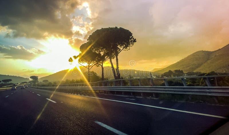 Belle vue panoramique sur la route, les montagnes et les arbres sur fond de ciel doré avec nuages roses et rayons du soleil photos libres de droits
