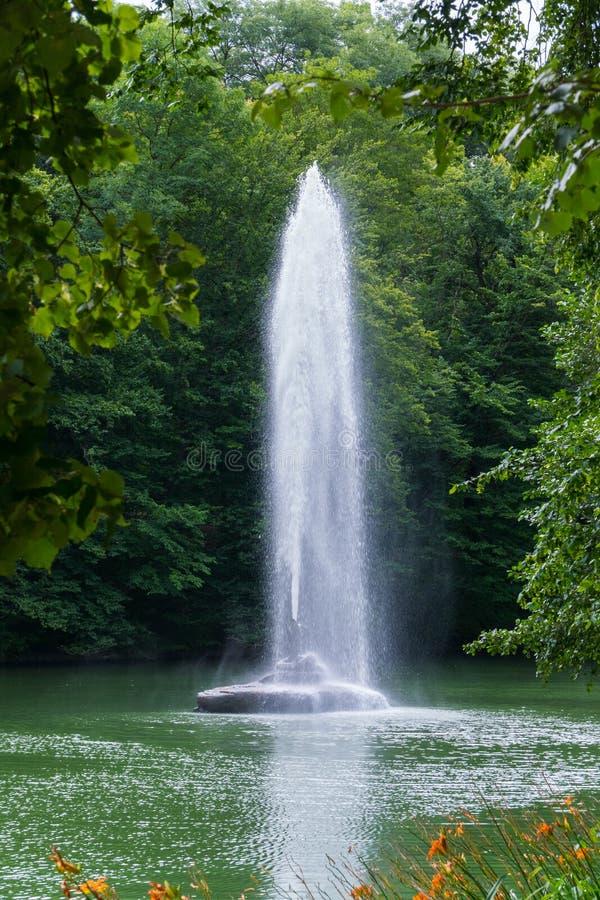 Belle vue par derrière le feuillage vert des arbres à la fontaine au milieu de l'étang avec un courant clair photographie stock libre de droits