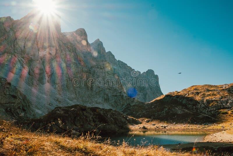 Belle vue scénique de petit lac en montagnes d'alpes avec la montagne rocheuse behing en hausse de rayons du soleil avec le ciel  image stock