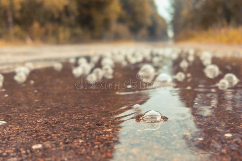 Bellen in een vulklei op de weg in de regen Het concept van de de herfstdroefheid stock fotografie