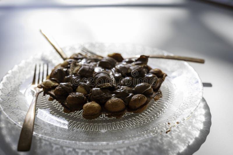 Bellenwafel met chocolade op een transparante plaat met een antiek ontwerp met gouden vork en mes op witte houten lijst stock foto