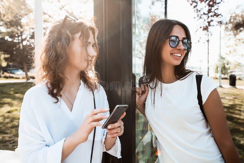 Belles amies heureuses se tenant sur un arrêt d'autobus photo stock