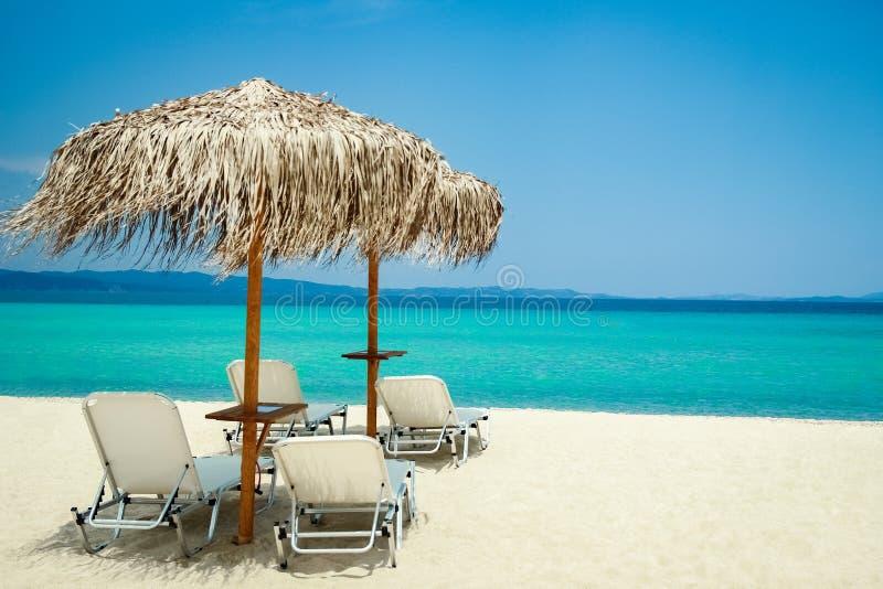 Belles chaises de plage près du bord de la mer de la Grèce sur le fond de nature photographie stock