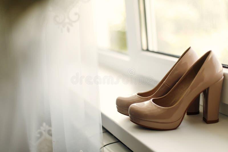 Belles chaussures beiges sur la fenêtre pendant le matin, morni nuptiale photos libres de droits