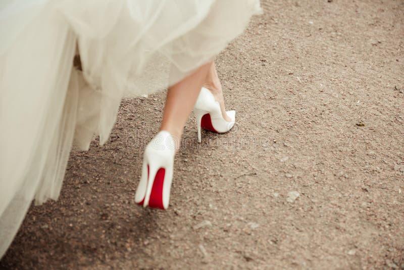 Belles chaussures du ` s de jeune mariée avec de longues jambes photographie stock