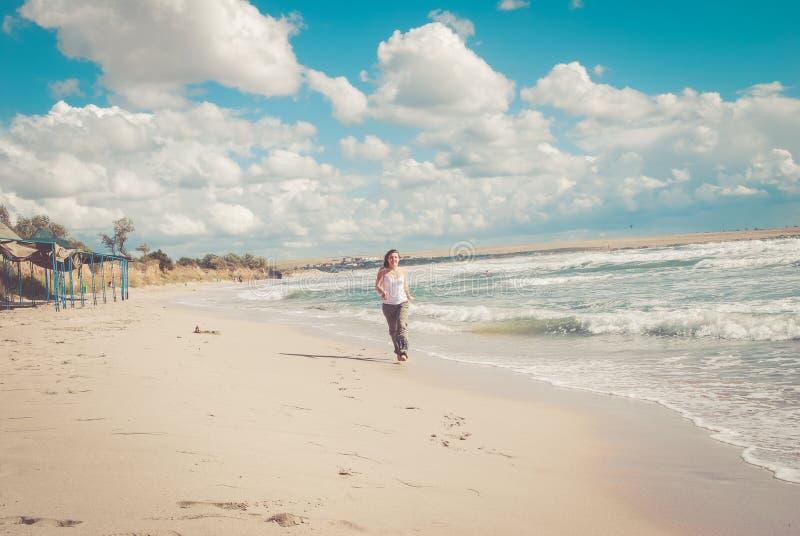 Belles courses de femme sur la plage photos stock